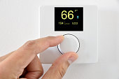 One hand adjust thermostat digital in  fahrenheit at home.Home automation