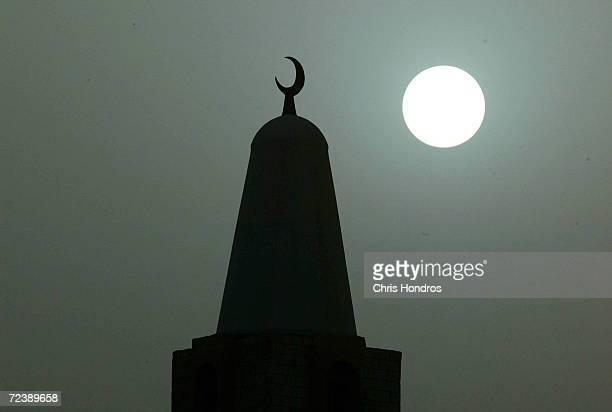 The sun appears behind the minaret of a mosque during a sandstorm March 19 2003 in Kuwait Coalition troop and equipment activity was stepped up today...