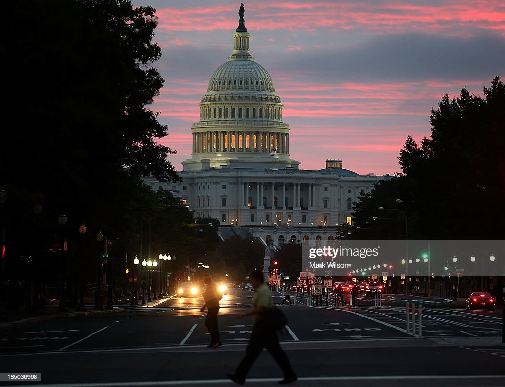The sun begins to rise behind the US Capitol building on the morning after a bipartisan bill was passed by the House and the Senate to reopened the...