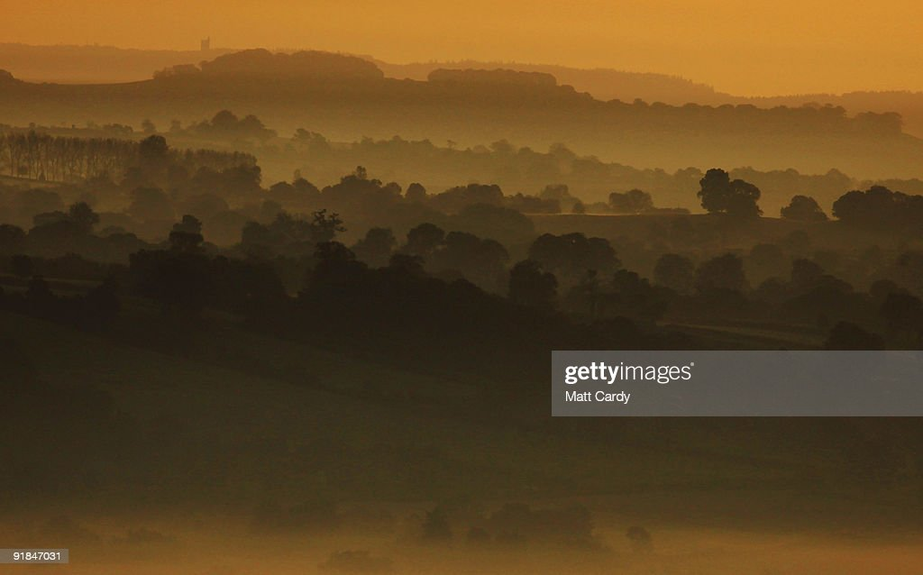 The sun begins to rise over the morning mist on the Somerset Levels viewed the distinctive landmark of the historic 15th century St. Michael's Tower, built on Glastonbury Tor on October 13, 2009 near Glastonbury, England. England, particularly in the south, is currently enjoying a spell of dry, fine weather, allowing the begining of the Autumn foliage colours - brought on by shortening daylight hours and cooler weather - to be fully appreciated.