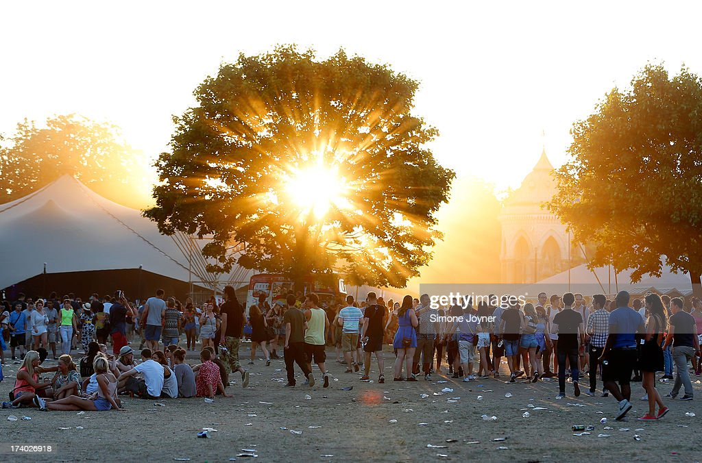 The sun begins to set brhind the trees as music fans make their way round the site on Day 1 of the Lovebox festival at Victoria Park on July 19, 2013 in London, England.