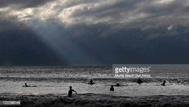 The sun breaks through as surfers hit the ocean off of Pawleys Island South Carolina Saturday August 27 after Hurricane Irene moved through the area...