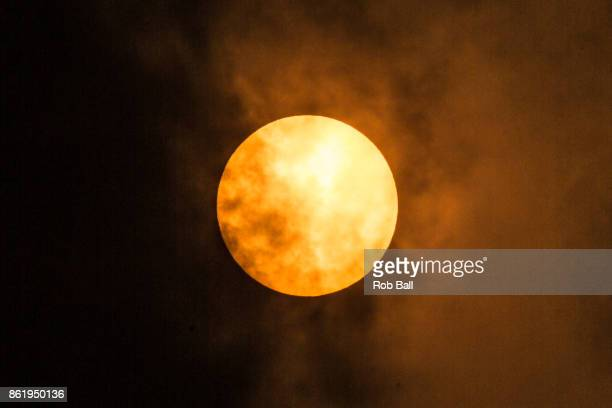 The sun goes a golden yellow colour due to dust from the Sahara being blown in with Storm Ophelia on October 16 2017 in Fulham London England