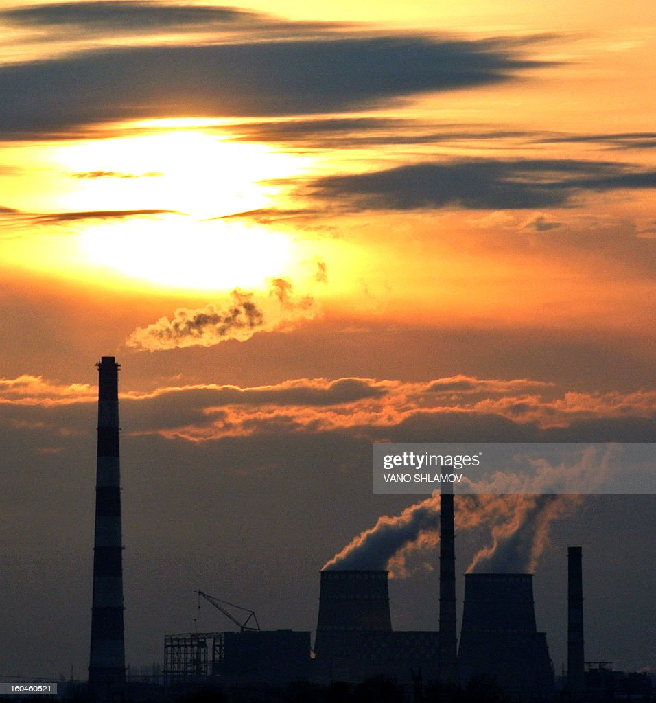 The sun goes up over chimneys and cooling towers discharging steam and smoke at a power plant in Rustavi, some 20 km outside the Georgia's capital Tbilisi, early on February 1, 2013.