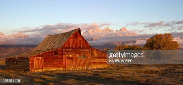 The sun hits the tips of the Grand Tetons behind the Moulton barn October 5 2012 in the Grand Teton National Park in Wyoming Grand Teton National...