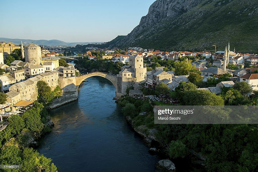 The sun illuminates the Old Bridge as the city of Mostar remembers the 1993 conflict on June 28, 2013 in Mostar, Bosnia and Herzegovina. The Siege of Mostar peaked in 1993 during the Croat-Bosniak conflict lasting eighteen months as fighting took place as Bosnia and Herzegovina declared independence from Yugoslavia. The city was divided in half between the two battling armies. Mostar, dating back over four hundred years, was mostly destroyed through the fighting. Although reconstruction has slowly commenced in the last decades, evidence of the war remains in bullet ravaged buildings still standing throughout the city.