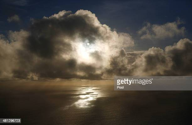 The sun is pictured through low clouds as a Royal New Zealand Air Force P3K2 Orion aircraft searches for missing Malaysian Airlines flight MH370 on...