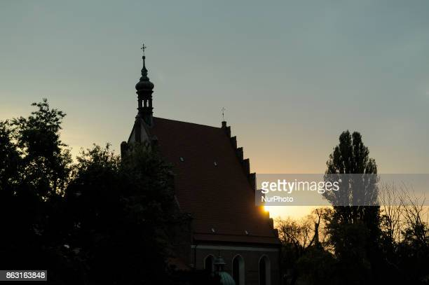 The sun is seen setting behind the St Martin and St Nicholas cathedral in Bydgoszcz Poland on 19 October 2017