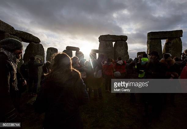 The sun makes a brief appearance through clouds as druids pagans and revellers gather in the centre of Stonehenge hoping to see the sun rise as they...