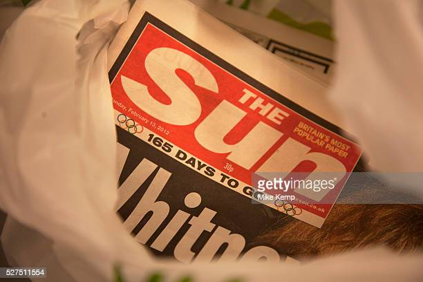 The Sun newspaper in a shopping bag in London England UK British police arrested five senior members of staff at News Corporation's newspaper The Sun...