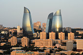 The Sun rise is reflected in The Flame Towers on August 4 2014 in Baku Azerbaijan