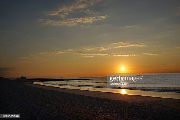 The sun rises along Rockaway Beach on the oneyear anniversary of Hurricane Sandy on October 29 2013 in the Queens borough of New York City Many...
