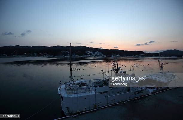 The sun rises as a fishing vessel is moored at the fish market in Kesennuma City Miyagi Prefecture on Friday March 7 2014 Reconstruction of Tohoku...