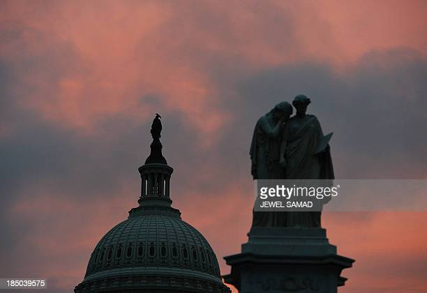 The sun rises as seen behind the US Capitol building on the morning after a bipartisan bill was passed by the House and the Senate to reopen the...