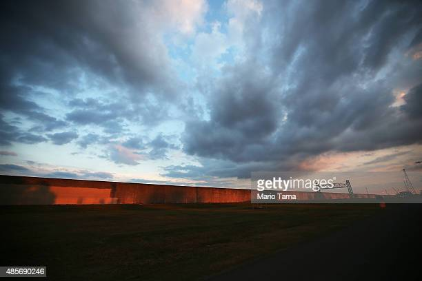 The sun rises at the reconstructed levee wall along the Industrial Canal in the Lower Ninth Ward on August 29 2015 in New Orleans Louisiana A levee...