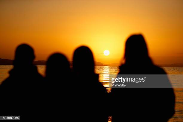 The sun rises behind athletes on the road to the Rio Olympic Games during the Olympic Games 100 days countdown ceremony at Cheltenham Beach on April...
