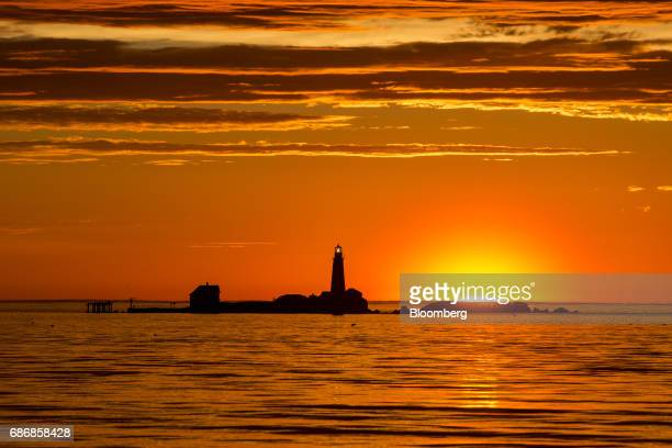 The sun rises behind the Boston Light on Little Brewster Island off of Hull Massachusetts US on Wednesday May 17 2017 New restrictions are coming to...