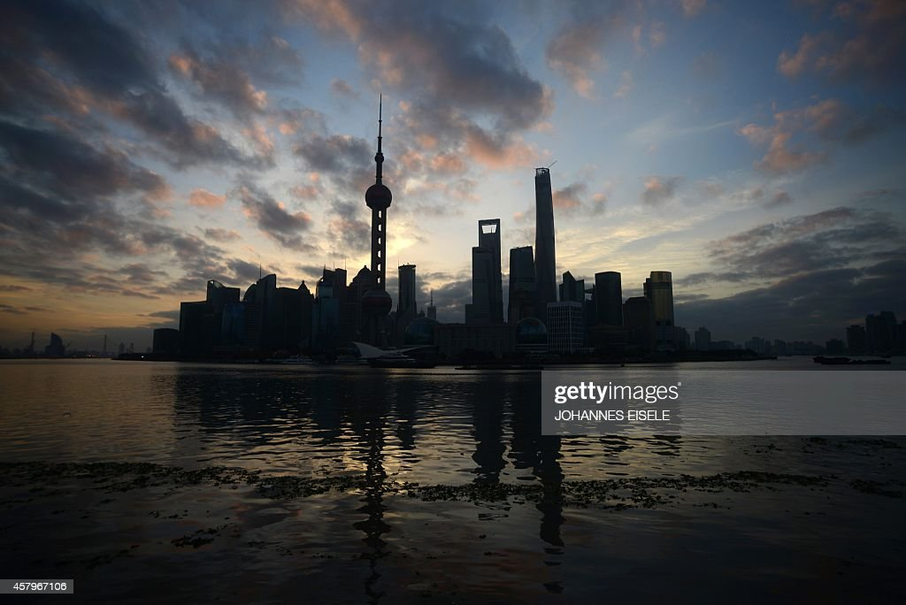 The sun rises behind the skyline of Pudong's Lujiazui Financial District in Shanghai on October 28 2014 The Chinese conomy expanded 73 percent in the...