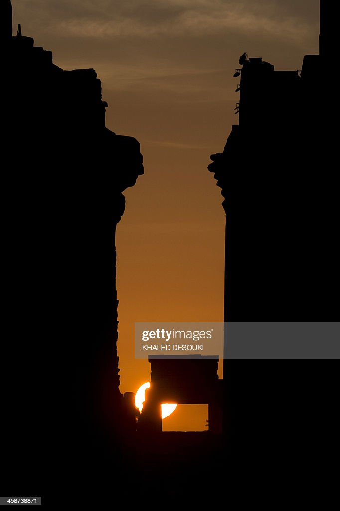 The sun rises behind the Temple of Karnak Temple during the alignment of the winter solstice sunrise to the temple in the southern Egyptian city of Luxor on December 21, 2013. The central sector of the site which takes up the largest amount of space, is dedicated to the Egyptian god Amun, who became prominent as the greatest of the gods.