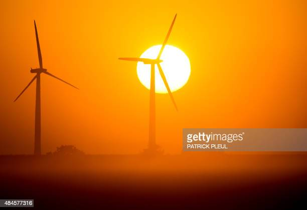 The sun rises behind wind turbines in Mallnow eastern Germany on August 20 2015 AFP PHOTO / DPA / PATRICK PLEUL GERMANY OUT / AFP PHOTO / DPA /...