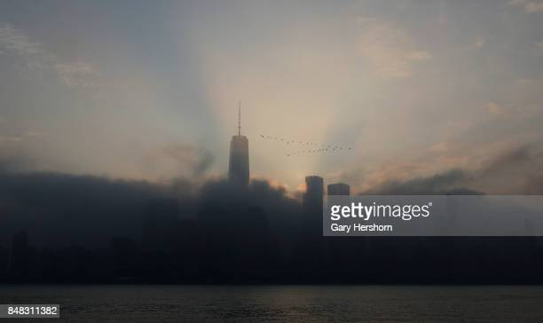The sun rises in the fog behind lower Manhattan and One World Trade Center as a flock of geese fly past in New York City on September 16 as seen from...