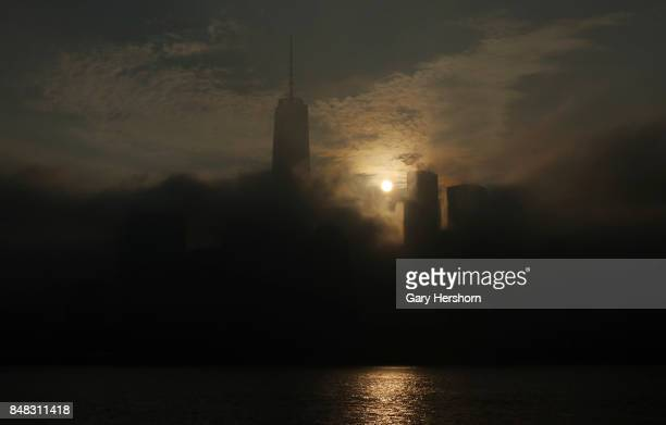 The sun rises in the fog behind lower Manhattan and One World Trade Center in New York City on September 16 as seen from Jersey City NJ