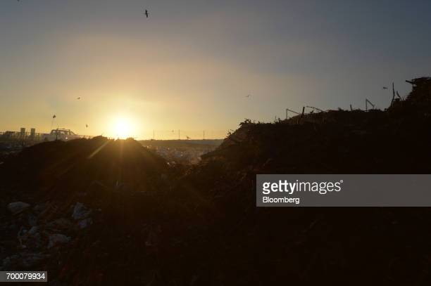 The sun rises over a landfill cell at the Melbourne Regional Landfill site operated by Cleanaway Waste Management Ltd at dawn in Ravenhall Victoria...