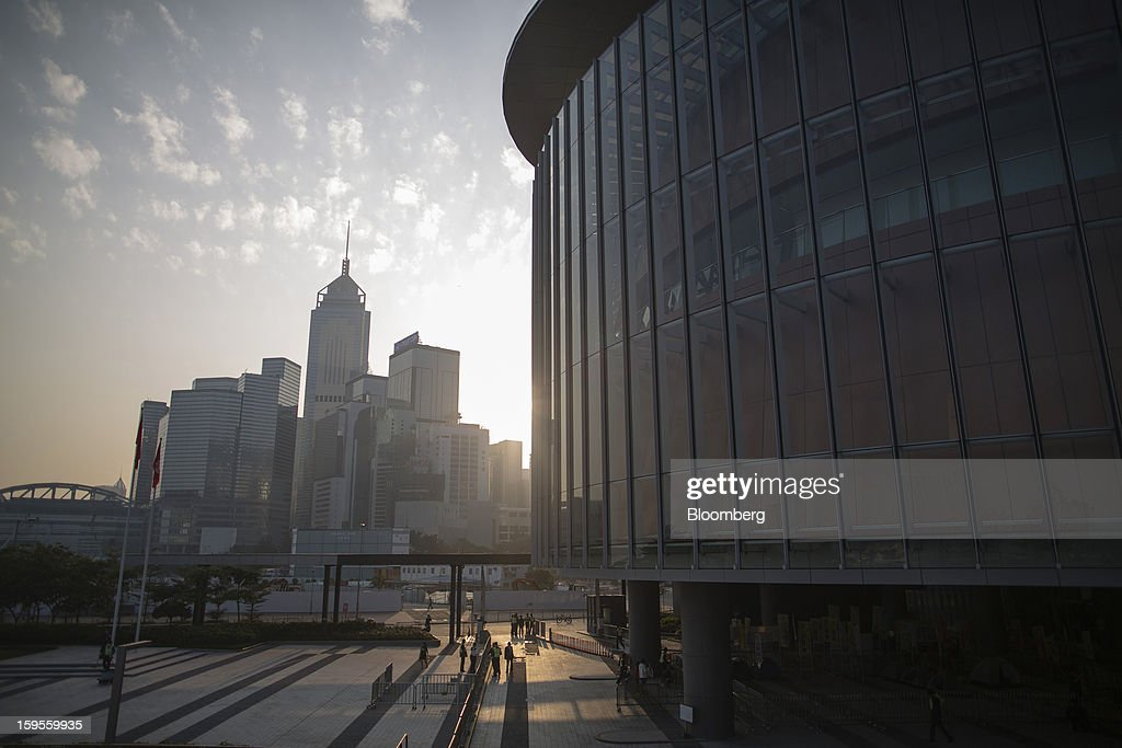 The sun rises over commercial buildings in the Wan Chai district, left, and the Legislative Council Complex, right, in Hong Kong, China, on Wednesday, Jan. 16, 2013. Hong Kong will maintain property curbs for overseas buyers as it seeks to meet the housing needs of its people, Chief Executive Leung Chun-ying said in his first policy address today. Photographer: Jerome Favre/Bloomberg via Getty Images