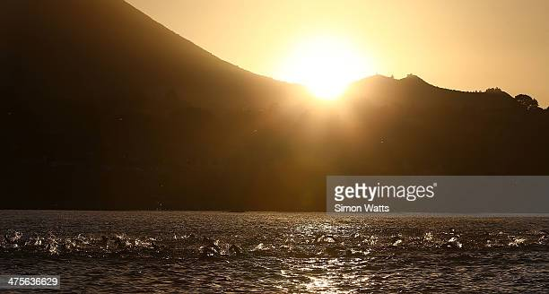 The sun rises over Lake Taupo during the swim leg of the New Zealand Ironman on March 1 2014 in Taupo New Zealand