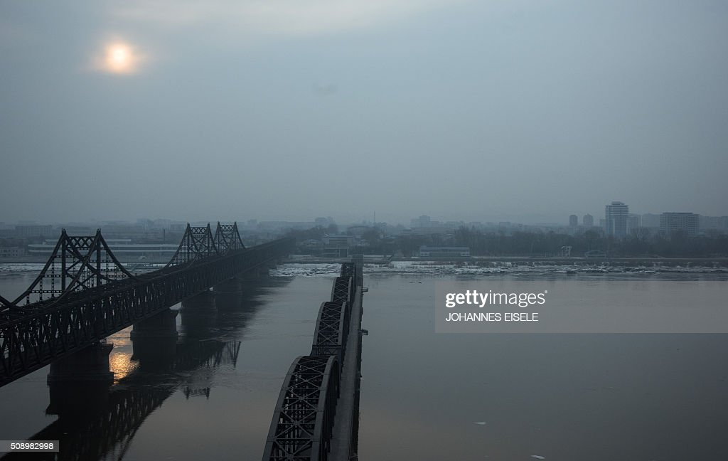 The sun rises over the banks of the Yalu River in the Chinese border town of Dandong, opposite to the North Korean town of Sinuiju, on February 8, 2016. The UN Security Council strongly condemned North Korea's rocket launch on February 7 and agreed to move quickly to impose new sanctions that will punish Pyongyang for 'these dangerous and serious violations.' With backing from China, Pyongyang's ally, the council again called for 'significant measures' during an emergency meeting held after North Korea said it had put a satellite into orbit with a rocket launch. AFP PHOTO / JOHANNES EISELE / AFP / JOHANNES EISELE