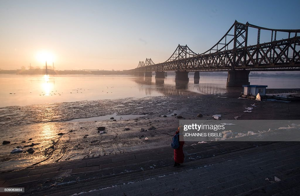 The sun rises over the bridge on the banks of the Yalu River in the Chinese border town of Dandong opposite to the North Korean town of Sinuiju on February 9, 2016. The UN Security Council strongly condemned North Korea's rocket launch on February 7 and agreed to move quickly to impose new sanctions that will punish Pyongyang for 'these dangerous and serious violations.' AFP PHOTO / JOHANNES EISELE / AFP / JOHANNES EISELE
