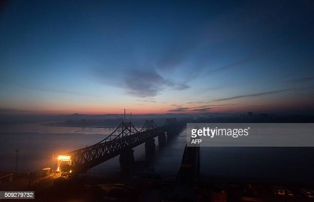 TOPSHOT The sun rises over the bridge on the banks of the Yalu River in the Chinese border town of Dandong opposite to the North Korean town of...