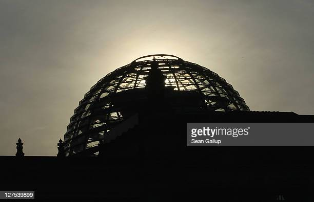 The sun rises over the cupola of the Reichstag home of the Bundestag on September 29 2011 in Berlin Germany Bundestag members are scheduled to vote...