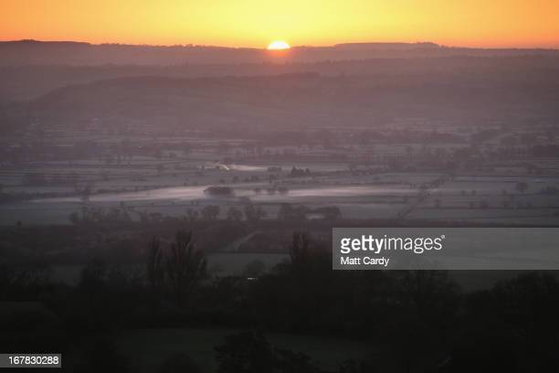 The sun rises over the Somerset Levels as people join in a Beltane dawn celebration service in front of St Michael's Tower on Glastonbury Tor on May...