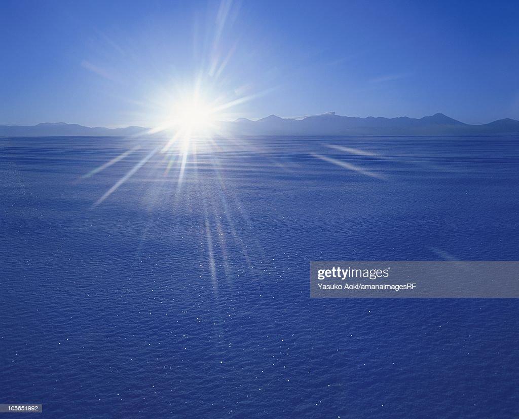 The Sun Rising Over A Snowy Field Hokkaido Japan Stock Photo ...