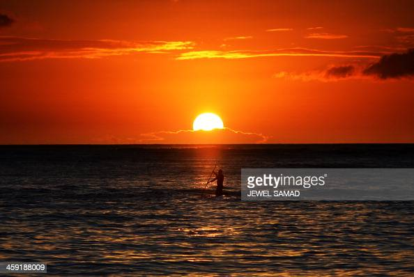 The sun set is seen from Waikiki beach in Honolulu Hawaii 2013 The US first family is in Hawaii for their annual holiday vacation AFP PHOTO/Jewel...