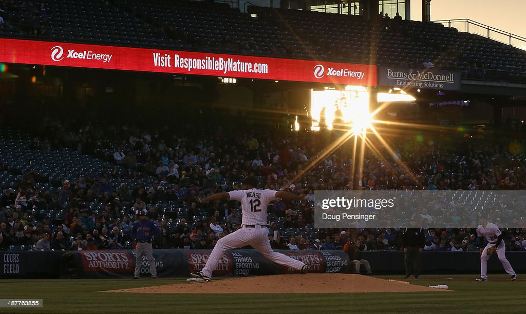 The sun sets as starting pitcher Juan Nicasio #12 of the Colorado Rockies works his way to a win against the New York Mets at Coors Field on May 1, 2014 in Denver, Colorado. The Rockies defeated the Mets 7-4.