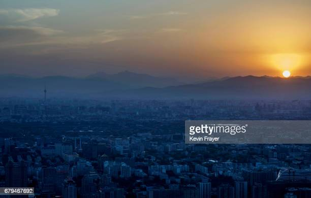 The sun sets as the air clears of dust from a sandstorm looking west on May 5 2017 over Beijing China Sandstorms are common in northern China during...
