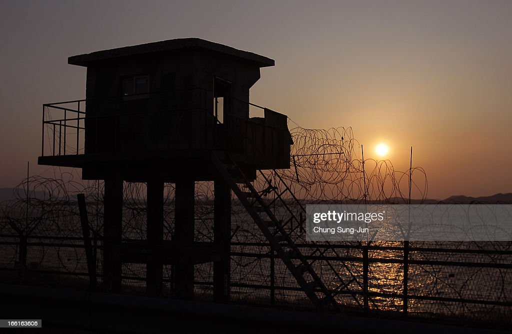 The sun sets behind a barbedwire fence and checkpoint near the border village of Panmunjom on April 9 2013 in Paju South Korea North Korea announced...