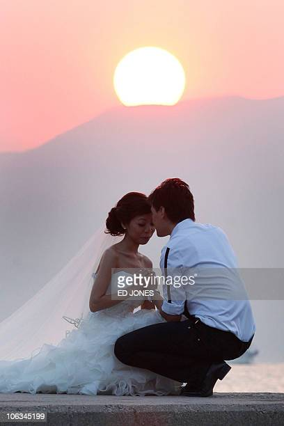 The sun sets behind a couple in wedding dress as they pose for photographers on a wall at a beach in the Stanley district of Hong Kong on October 29...