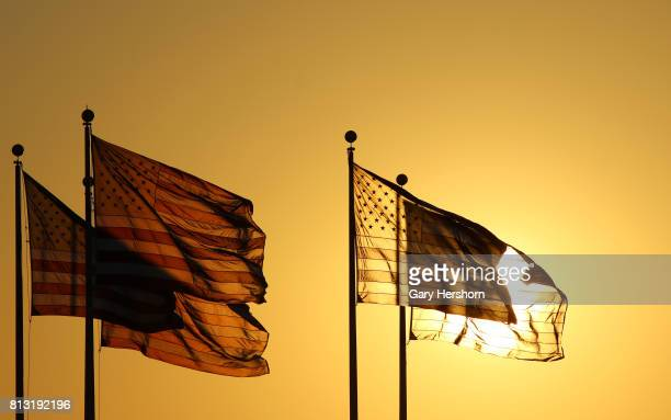 The sun sets behind a grpoup of US flags at Liberty State Park on July 9 2017 in Jersey City New Jersey