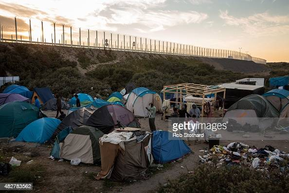 The sun sets behind a make shift camp near the port of Calais on August 2 2015 in Calais France Hundreds of migrants are continuing to attempt to...
