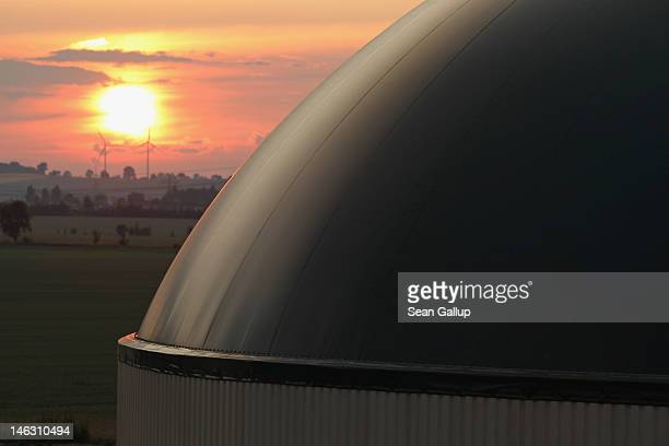 The sun sets behind a new biogas plant in Lower Saxony on June 12 2012 near Ebendorf Germany The plant processes natural waste from local farms into...