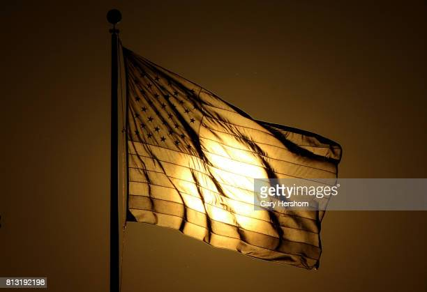 The sun sets behind a US flag at Liberty State Park on July 9 2017 in Jersey City New Jersey