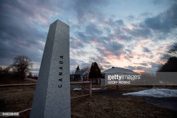 The sun sets behind an abandoned customs station on the US side of the Canada/US border on Meridian Road in Champlain New York February 27 2017 / AFP...