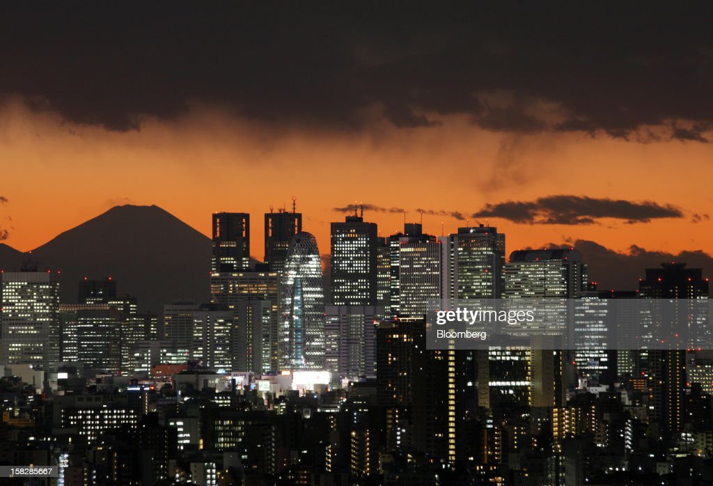 The sun sets behind buildings in front of Mount Fuji in Tokyo, Japan, on Wednesday, Dec. 12, 2012. Japan's economy shrank in the last two quarters, meeting the textbook definition of a recession, as the dispute with China, the country's biggest export market, caused consumers there to shun Japanese products and contributed to Japan's worst year for exports since the global recession in 2009. Photographer: Tomohiro Ohsumi/Bloomberg via Getty Images