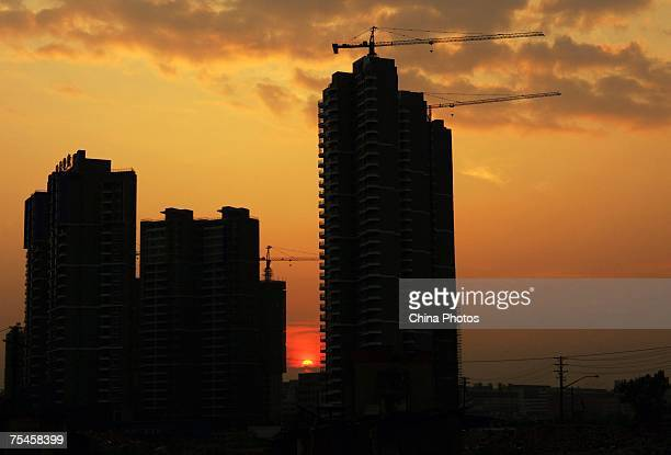 The sun sets behind buildings under construction n July 17 2007 in Wuhan of Hubei Province China Research shows that from 2003 to 2006 the average...
