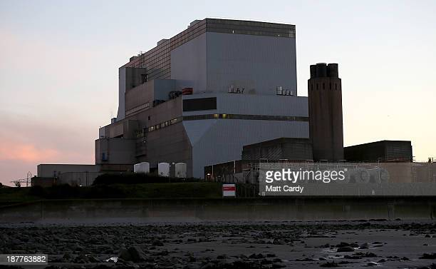 The sun sets behind Electricite de France SA's Hinkley Point B nuclear power station besides the Bristol Channel near Bridgwater on November 12 2013...