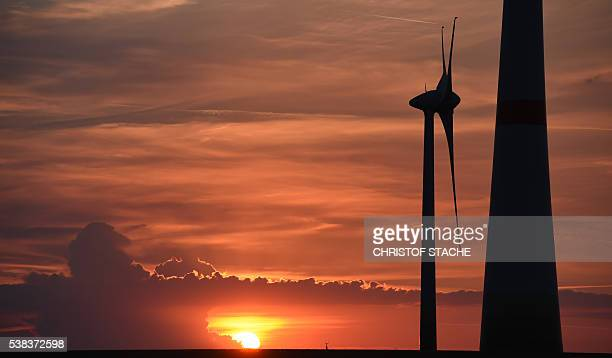 The Sun sets behind of a wind power station at a field near the small village Groebitz near Leipzig Germany on June 5 2016 / AFP / CHRISTOF STACHE