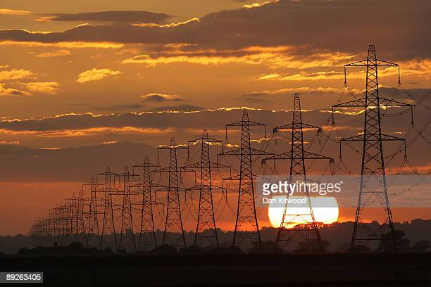 The sun sets behind power lines running from Dungerness nuclear power station on July 25 2009 near Lydd United Kingdom